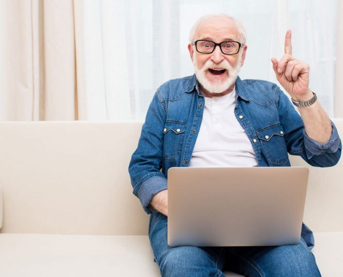 elderly man with laptop posting his finger up saying: got it