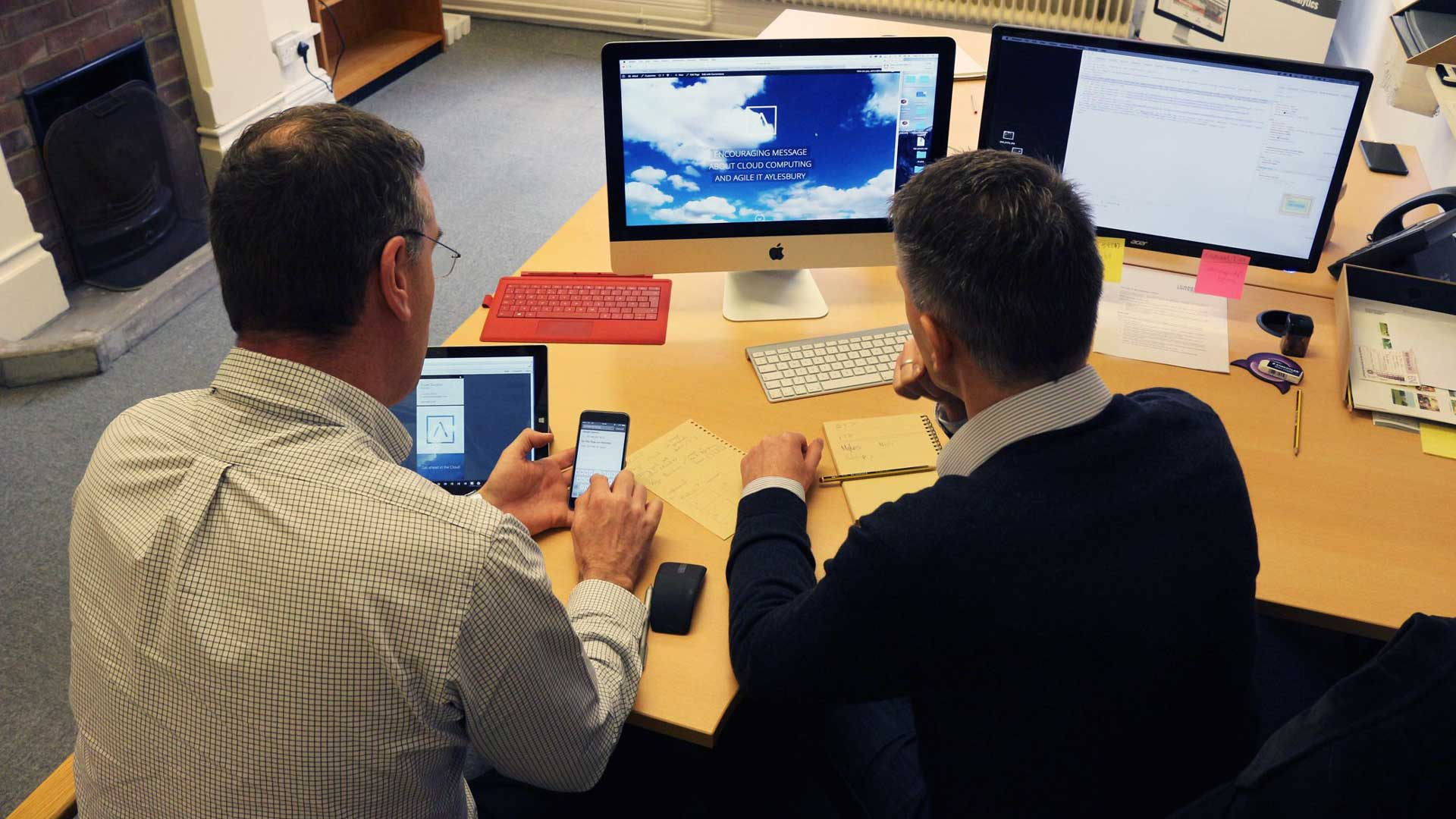 two people comparing web design on mobile phone and on a computer screen